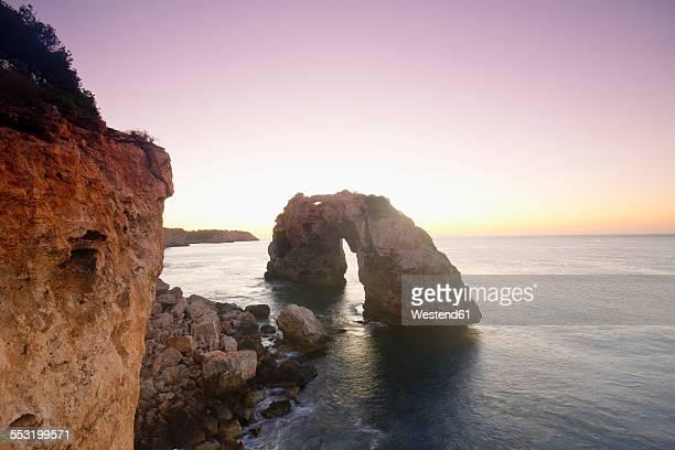 Spain, Mallorca, Es Pontas, stone arch at twilight