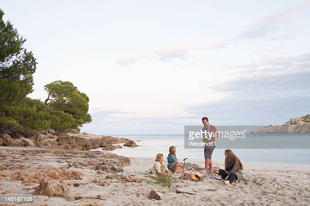 Spain, Mallorca, Friends at camp fire on beach