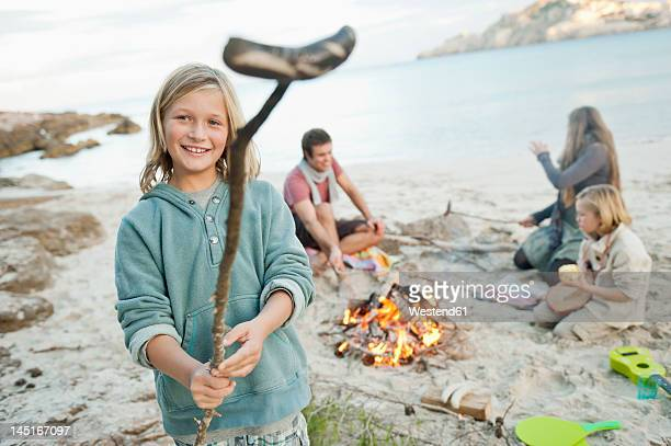 Spain, Mallorca, Friends with sausages at camp fire on beach