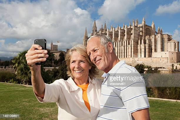 Spain, Mallorca, Palma, Senior couple smiling taking picture with Cathedral Santa Maria, portrait