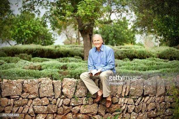 Spain, Mallorca, portrait of relaxed senior man sitting with a book on a wall in the garden