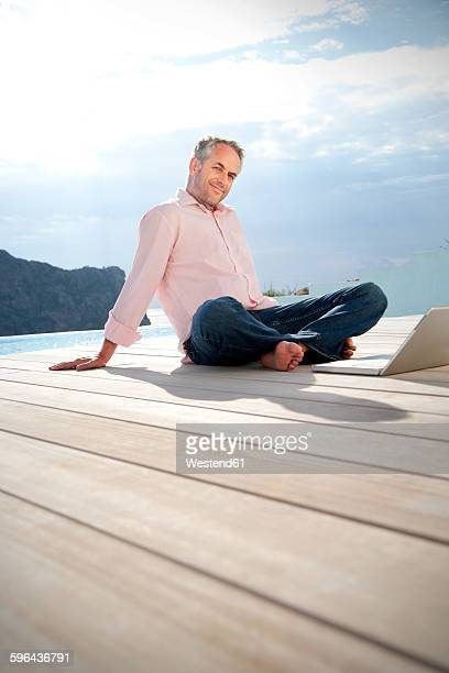 Spain, Mallorca, portrait of smiling man sitting in front of a pool with laptop