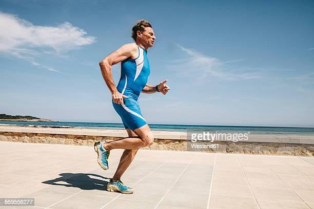 Spain, Mallorca, Sa Coma, triathlet running along beach promenade