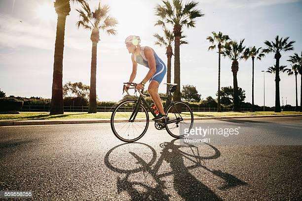 Spain, Mallorca, Sa Coma, triathlet training on bicycle