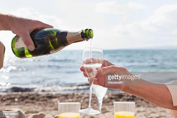 Spain, Mallorca, Senior couple drinking sparkling wine at beach