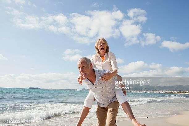 Spain, Mallorca, Senior man giving piggy back ride to woman at beach