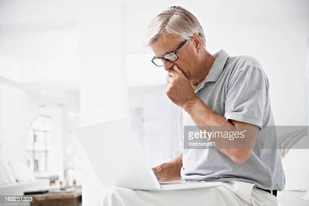Spain, Mallorca, Senior man receiving bad news in laptop