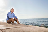 Spain, Mallorca, Senior man sitting at sea shore
