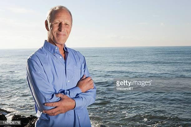 Spain, Mallorca, Senior man standing at sea shore, portrait