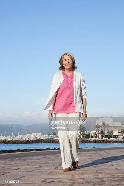 Spain, Mallorca, Senior woman walking along sea shore, smiling