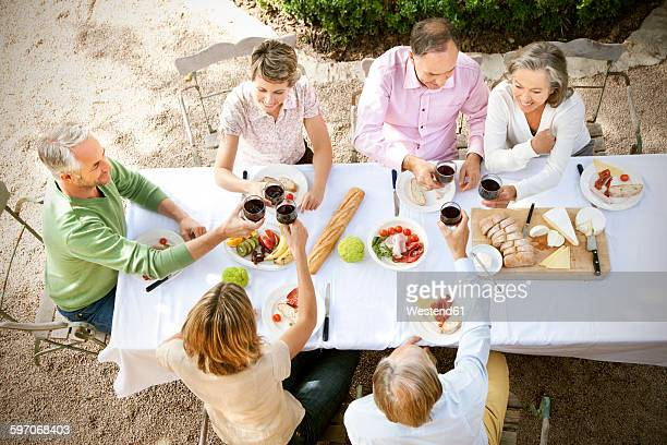 Spain, Mallorca, six friends sitting at laid table in the garden toasting with red wine