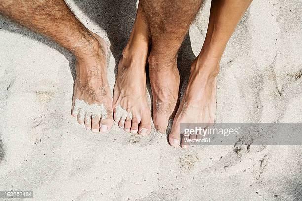 Spain, Mid adult couple legs on beach