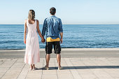 Spain, Mid adult couple standing at Atlantic Ocean, looking at view