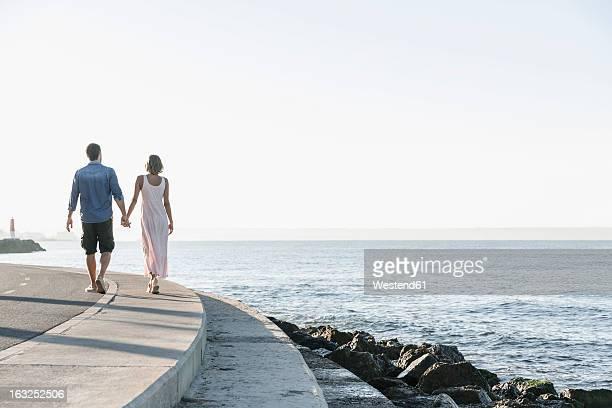 Spain, Mid adult couple walking along coast