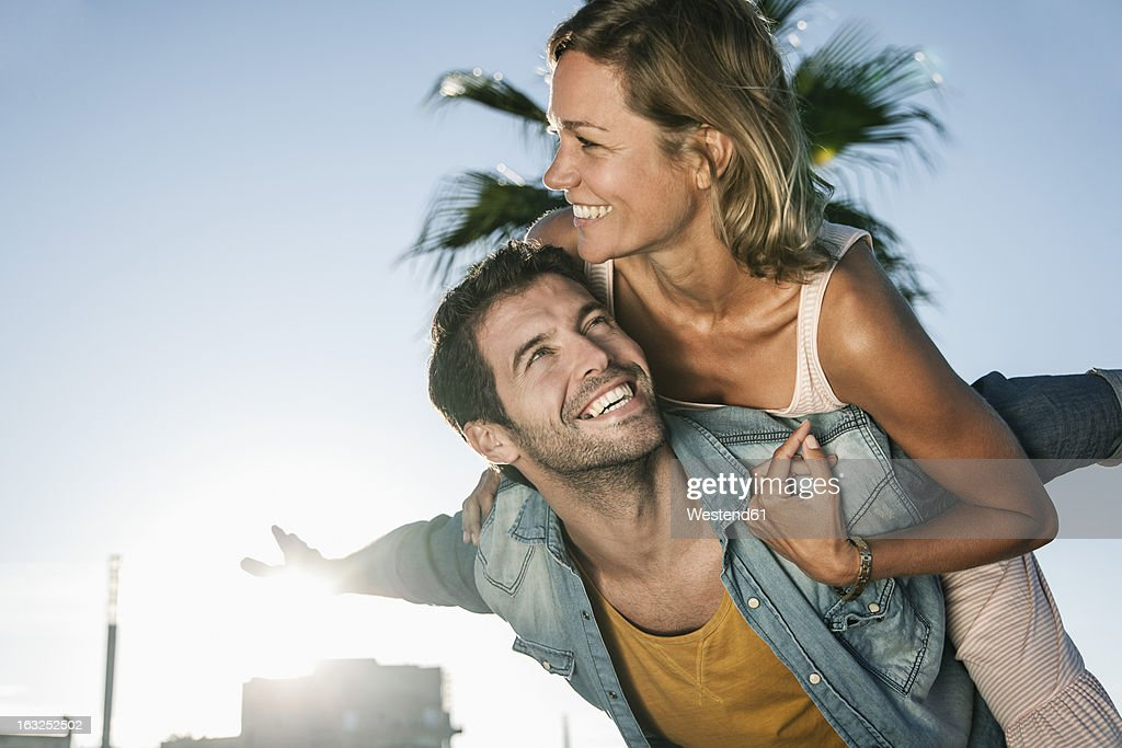 Spain, Mid adult man giving piggy back ride to woman : Photo