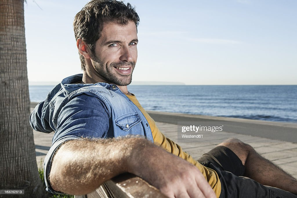 Spain, Mid adult man sitting on bench, smiling, portrait