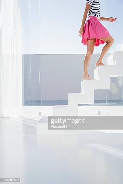 Spain, Mid adult woman walking up stairway