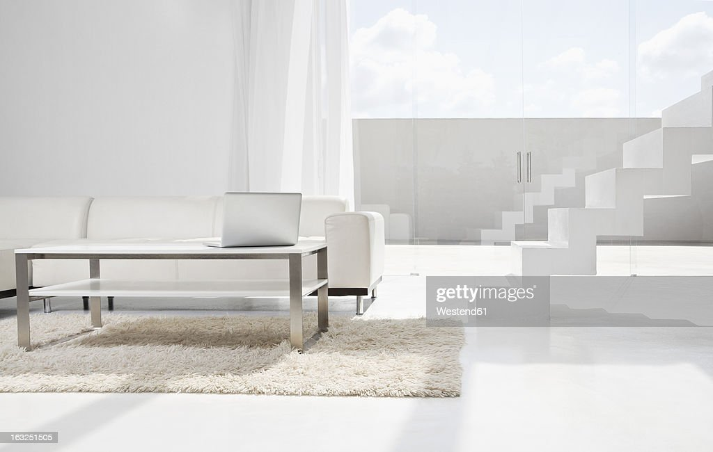 Spain, Modern living room with laptop and stairs