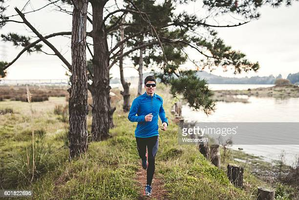 Spain, Naron, jogger running on a path in the shore of the sea