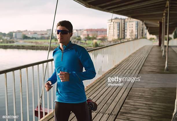 Spain, Naron, jogger running on a wooden bridge
