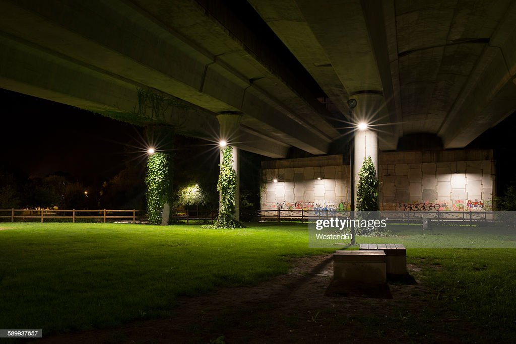 Spain, Naron, park under highway bridge lighted by street lamps at night