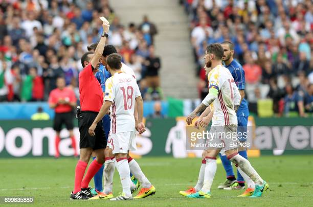 Spain players surround referee Cuneyt Cakir before he brandishes the yellow card to Spain's Sergio Busquets