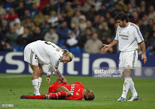 Real Madrid's players David Beckham and Luis Figo come to see Monaco's Patrice Evra hurt during their Champions League quarterfinal first leg...