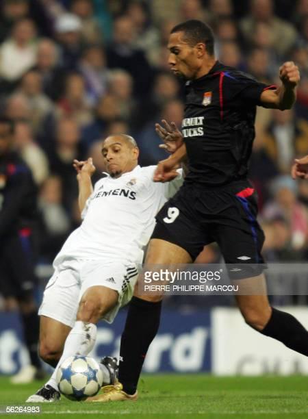 Real Madrid's Roberto Carlos tackles Lyon's John Carew during their Champions League group F football match at the Santiago Barnabeu Stadium in...