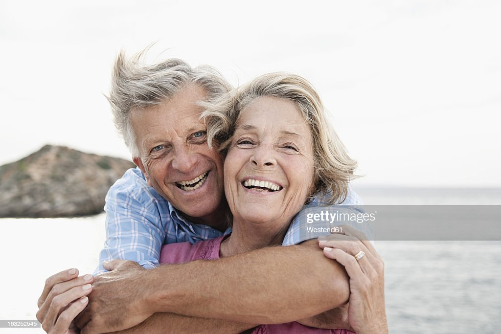 Spain, Senior couple embracing at harbour, smiling