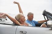 Spain, Senior couple in convertible car, smiling