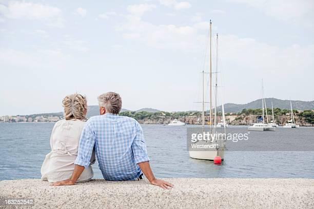 Spain, Senior couple sitting at harbour