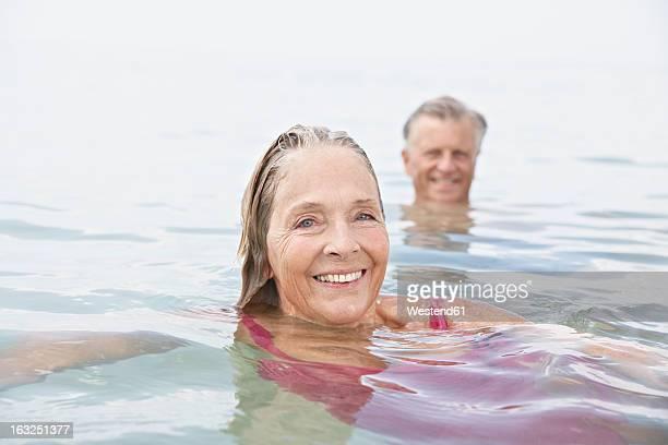 Spain, Senior couple swimming in sea