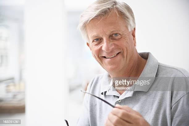 Spain, Senior man holding glasses, smiling, portrait