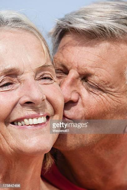 Spain, Senior man kissing to woman, close up