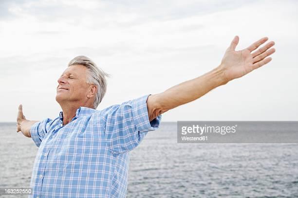 Spain, Senior man stretching on beach