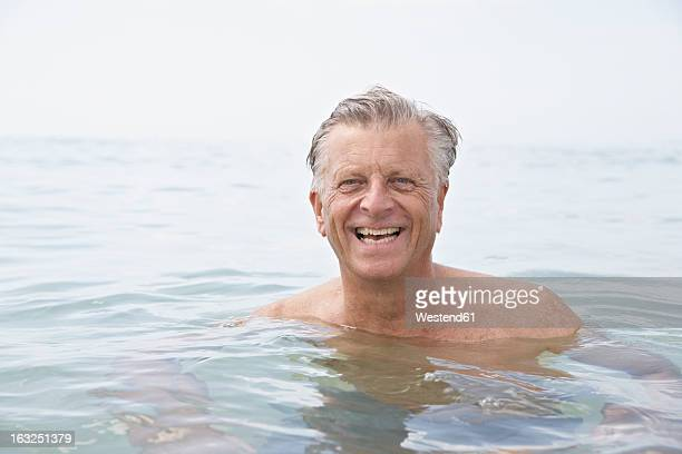 Spain, Senior man swimming in sea