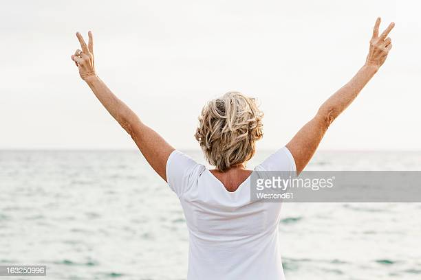 Spain, Senior woman exercising on jetty at the sea