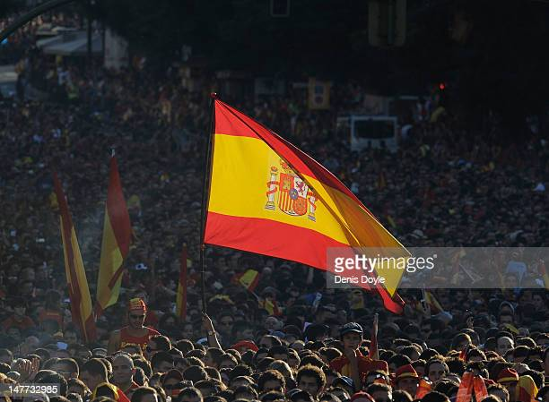 Spain supporter flies the national flag as large crowds wait for the arrival of the Spain team parading the UEFA EURO 2012 trophy on a doubledecker...