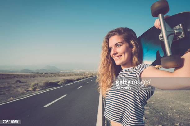 Spain, Tenerife, portrait of smiling young woman with longboard standing at empty country road