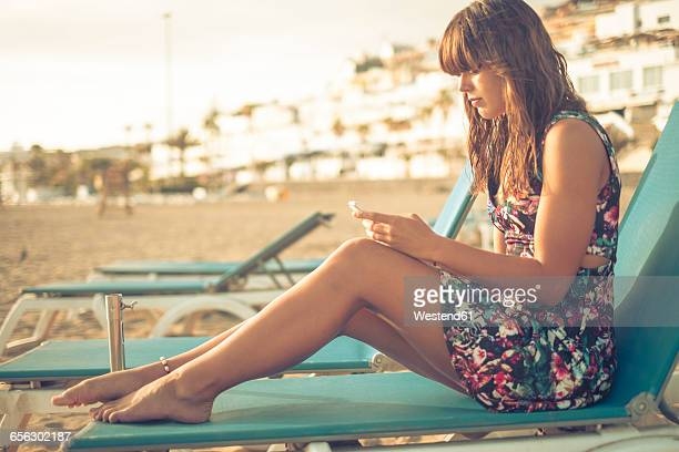 Spain, Tenerife, young woman with smartphone sitting on beach lounger
