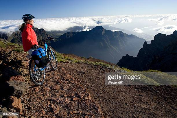 Spain, The Canary Islands, La Palma, Woman with mountain bike looking at mountain scenery