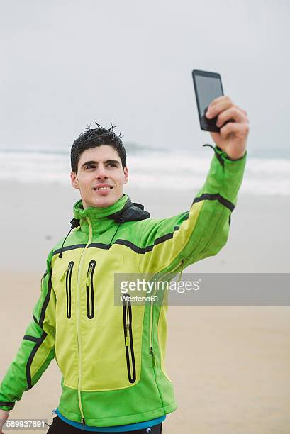 Spain, Valdovino, young jogger taking a selfie with smartphone on the beach at rainy day