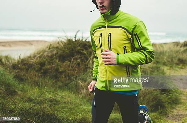 Spain, Valdovino, young man jogging on the beach at rainy day