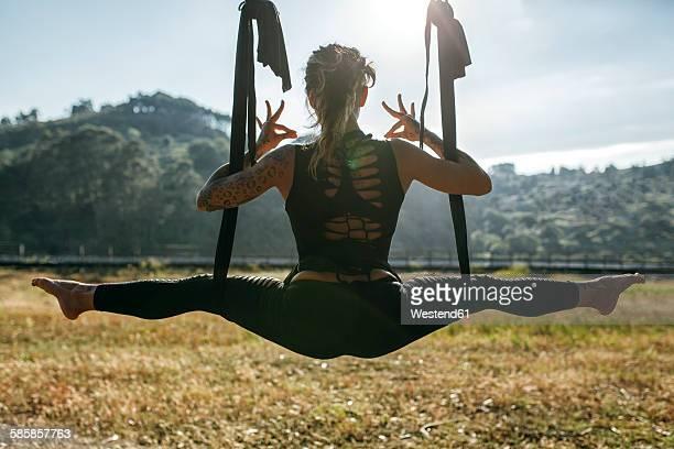 Spain, Villaviciosa, woman practicing aerial yoga outdoors