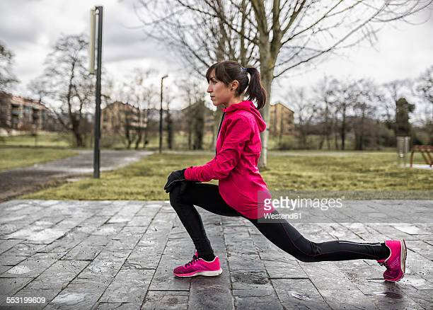 Spain, Young woman warming up in park