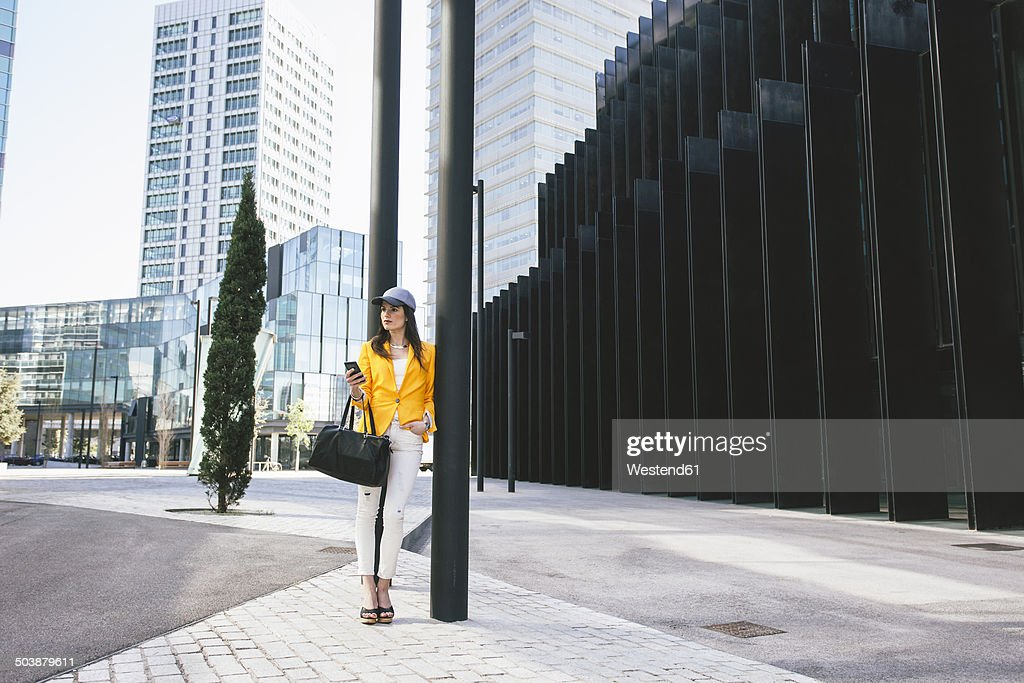 Spain,Catalunya, Barcelona, young modern woman with yellow jacket leaning against street lamp