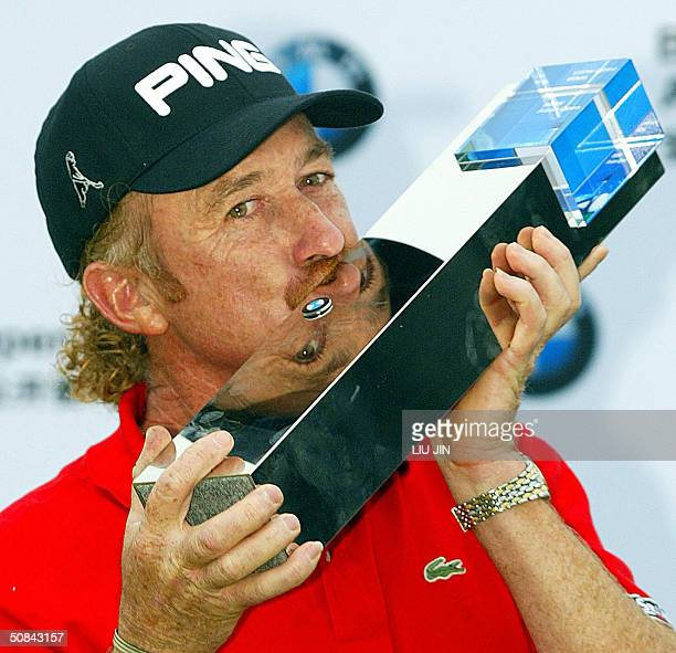 Spainish golfer Miguel Angel Jimenez kisses the championship trophy as he celebrates his victory at the awards ceremony after the final round of the...