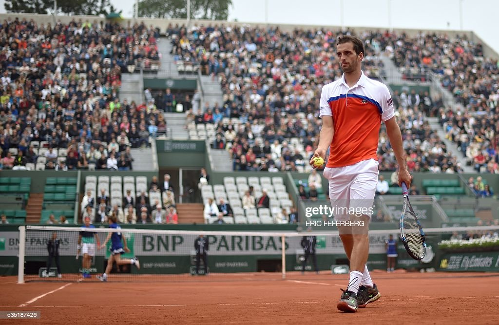 Spain's Albert Ramos-Vinolas prepares to serve the ball to Canada's Milos Raonic during his men's fourth round match at the Roland Garros 2016 French Tennis Open in Paris on May 29, 2016. / AFP / Eric FEFERBERG