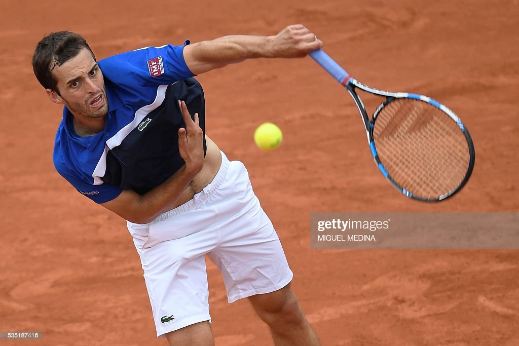 Spain's Albert Ramos-Vinolas serves the ball to Canada's Milos Raonic during his men's fourth round match at the Roland Garros 2016 French Tennis Open in Paris on May 29, 2016. / AFP / MIGUEL