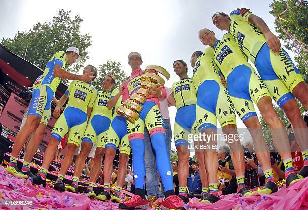 Spain's Alberto Contador celebrates with his trophy flanked by his TinkoffSaxo teammates on the podium after winning the 98th Giro d'Italia Tour of...